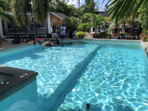 ダーウィンのダイビングリゾートでビールを飲んで、プールで泳ぐ